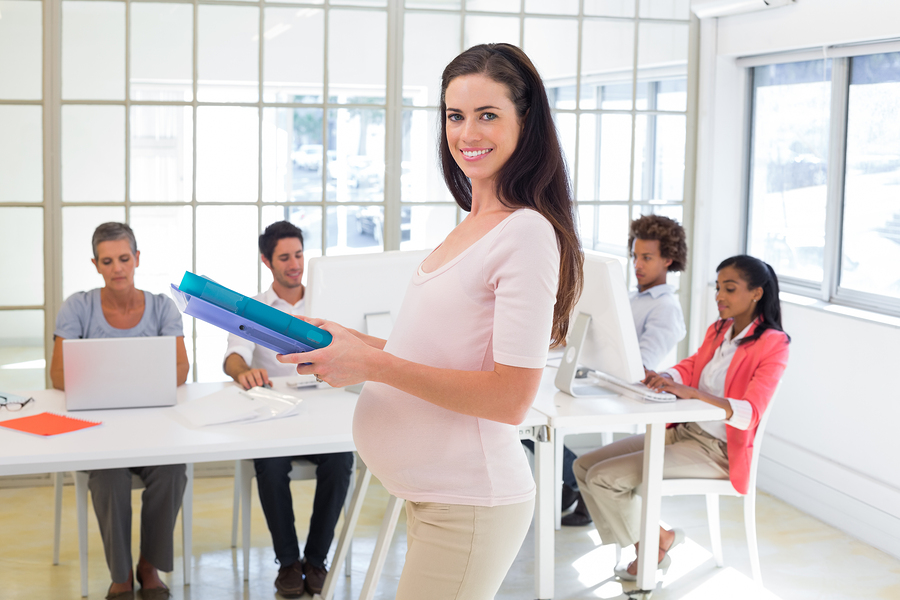 Pregnant office worker walking with folders in the office