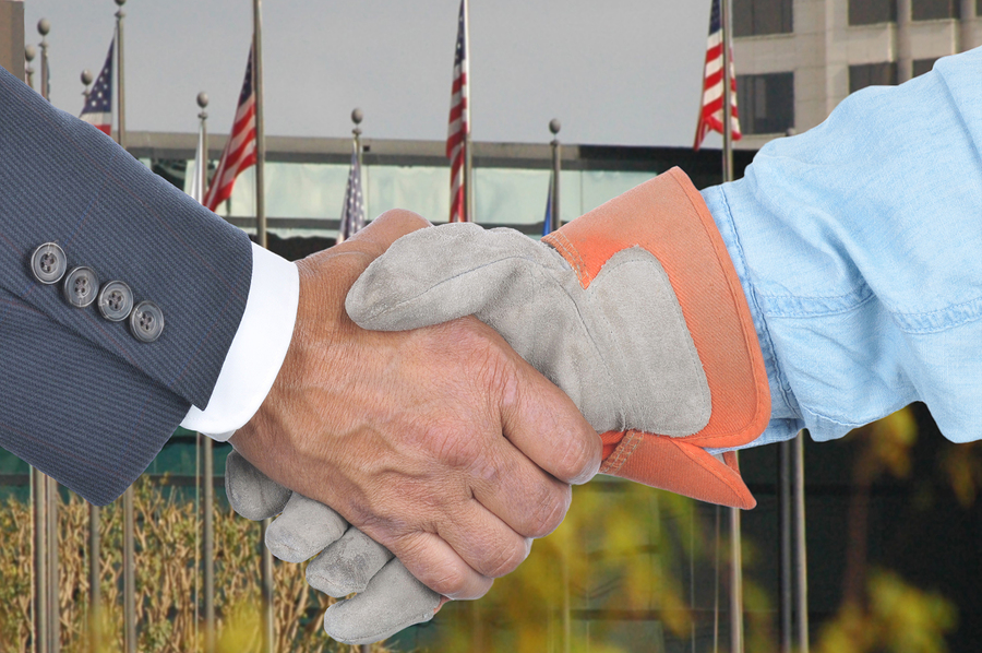 Closeup of Management and Labor handshake in front of building a