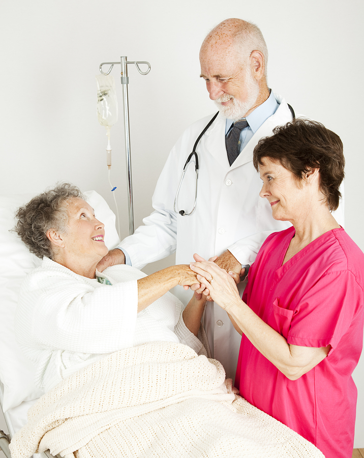 Attentive doctor and nurse caring for an elderly hospital patien