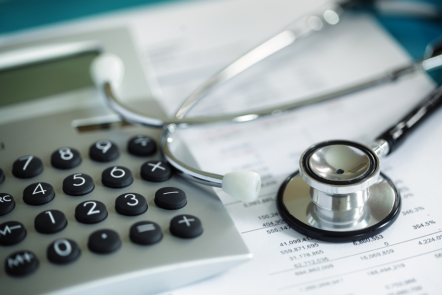Calculator and stethoscope on financial statement concept for fi