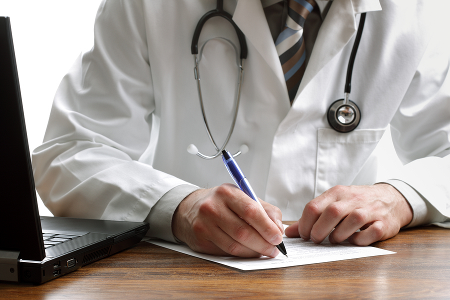 Doctor writing patient notes on a medical examination or prescription