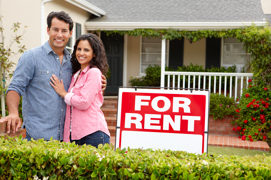 Hispanic couple outside home for rent